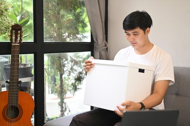 Jovem sorridente está segurando uma caixa de papelão com algo emocionante dentro.