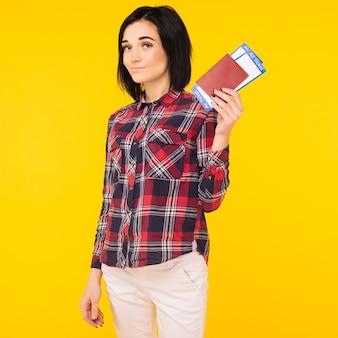 Jovem sorridente estudante animado segurando o bilhete do cartão de embarque do passaporte isolado no fundo amarelo. educação em faculdade no exterior. voo de viagem aérea - imagem