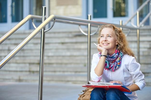 Jovem sorridente estudante mulher escrevendo e lendo o livro nas escadas da universidade ou faculdade, preparando-se para os exames.