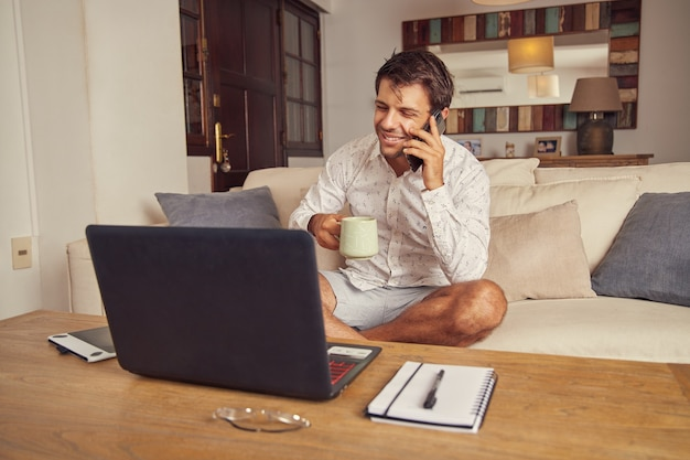 Jovem sorridente, falando ao telefone e bebendo café na frente de seu laptop no sofá em casa. ele faz teletrabalho, usa camisa branca e shorts.