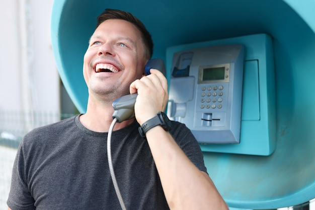 Jovem sorridente, falando na cabine telefônica na rua. conceito de comunicação por telefone fixo