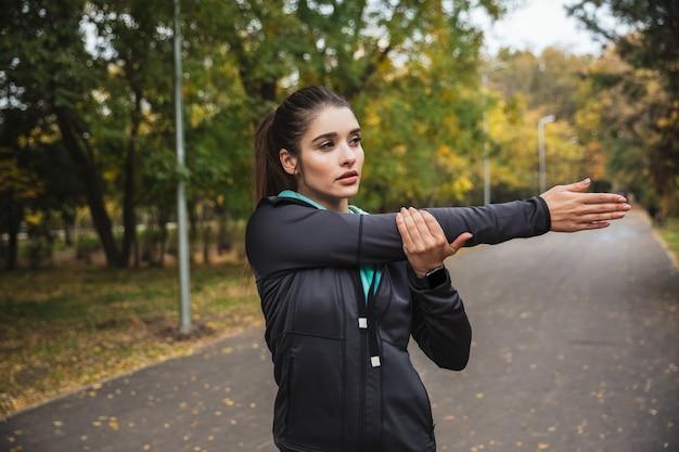 Jovem sorridente fazendo exercícios no parque