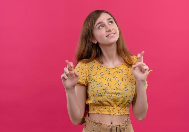 Jovem sorridente fazendo gestos de dedos cruzados e olhando para cima na parede rosa isolada com espaço de cópia