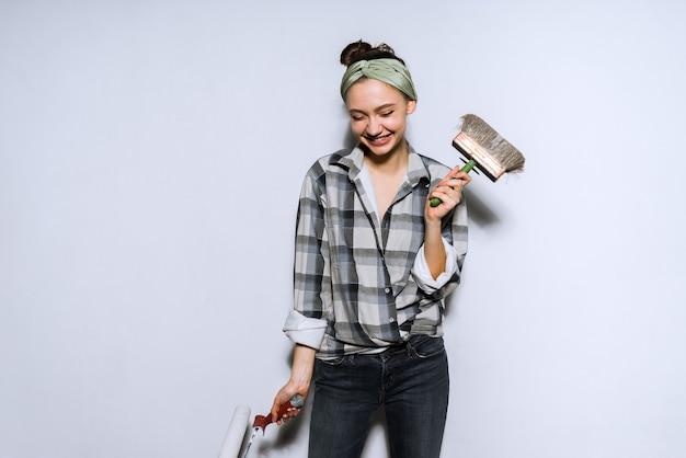 Jovem sorridente fazendo reparos em seu apartamento, segurando um pincel e um rolo nas mãos