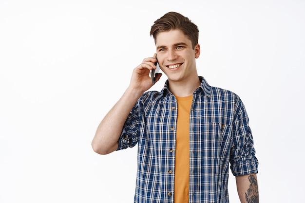 Jovem sorridente fazendo uma ligação telefônica, ligando para alguém e conversando no smartphone, olhando para o lado casualmente, parado no branco