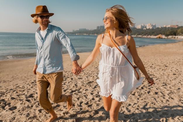 Jovem sorridente feliz com chapéu e mulher loira com vestido branco correndo juntos na praia nas férias de verão viajando