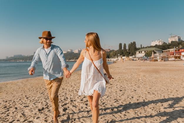 Jovem sorridente feliz com chapéu e mulher loira correndo juntos na praia nas férias de verão viajando