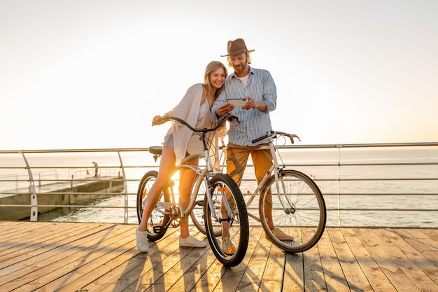Jovem sorridente feliz e feliz viajando de bicicleta usando smartphone