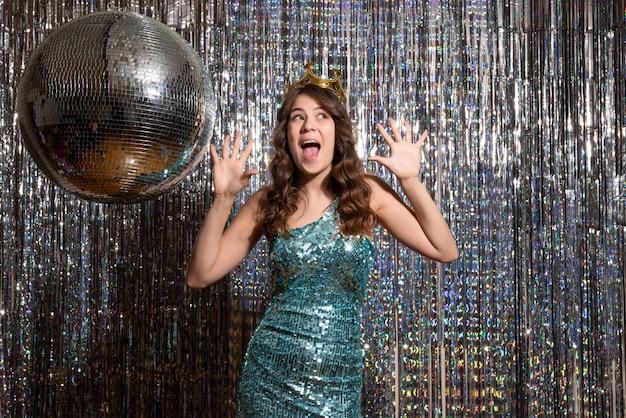 Jovem sorridente feliz encantadora usando um vestido azul verde brilhante com lantejoulas com coroa e apontando para cima na festa