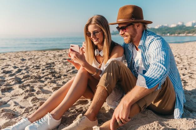 Jovem sorridente, feliz, homem e mulher com óculos de sol, sentado na praia de areia tirando uma foto de selfie na câmera do telefone