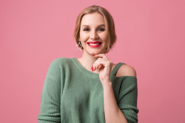 Jovem sorridente feliz mulher atraente, lábios vermelhos e esmalte para unhas, estilo casual, suéter verde, alegre, emoção positiva, modelo posando no estúdio, isolado, fundo rosa, olhando na câmera