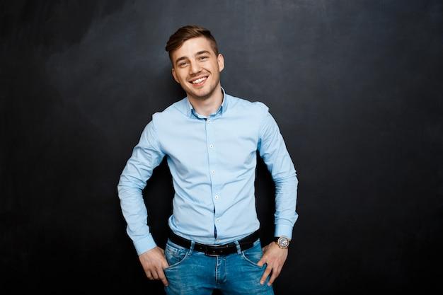 Jovem sorridente feliz na camisa azul sobre o quadro-negro