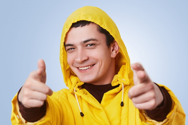 Jovem sorridente feliz usa anoraque amarelo e capuz, aponta para você com uma expressão alegre, escolhe alguém, isolado sobre o azul