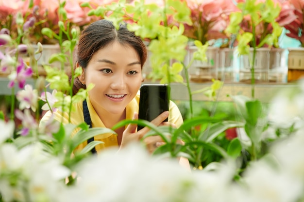 Jovem sorridente fotografando flores em uma estufa para vender nas redes sociais