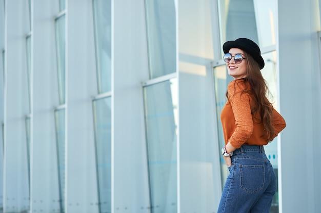 Jovem sorridente garota usando chapéu preto elegante