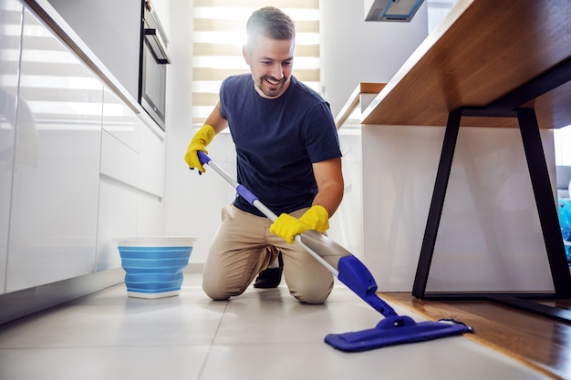 Jovem sorridente homem barbudo positivo ajoelhado no chão da cozinha, usando o esfregão e experimentando um novo produto de limpeza.