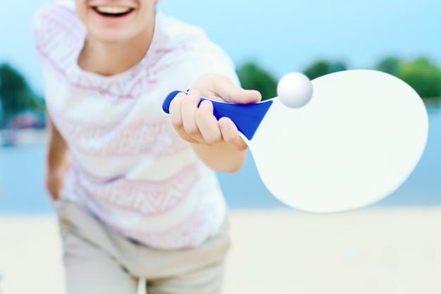 Jovem sorridente homem com roupas leves está chutando bola com raquete de matkot branco na mão.