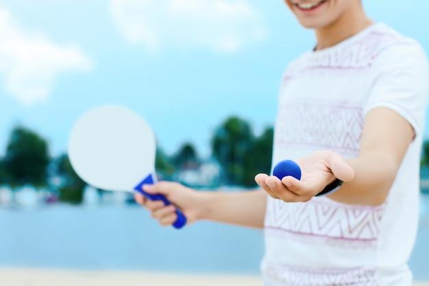 Jovem sorridente homem com roupas leves está segurando uma bola e raquete branca nas mãos.