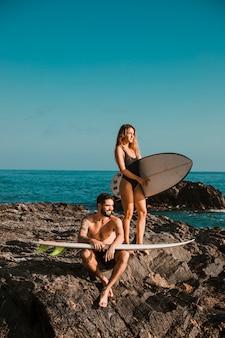 Jovem sorridente homem e mulher com pranchas de surf na rocha perto do mar