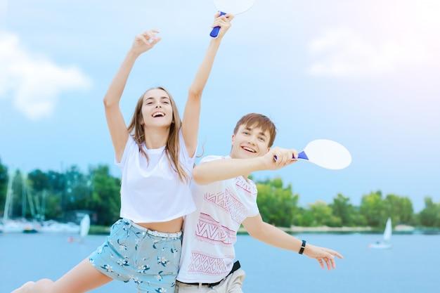 Jovem sorridente homem e mulher com roupas leves estão jogando matkot na natureza.
