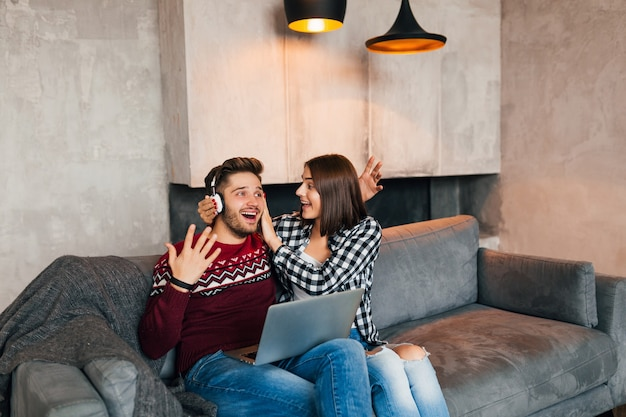 Jovem sorridente homem e mulher sentada em casa no inverno segurando no laptop ouvindo fones de ouvido com expressão de surpresa no rosto chocado, usando a internet