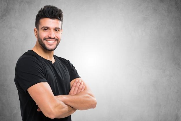 Jovem sorridente homem na frente de um muro de concreto