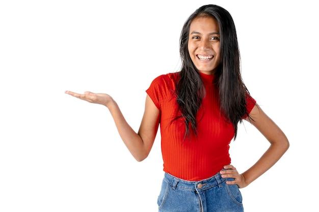 Jovem sorridente latina de cabelos escuros com a mão direita estendida para o lado em um fundo branco puro.