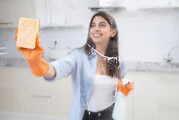 Jovem sorridente lavando janela em casa