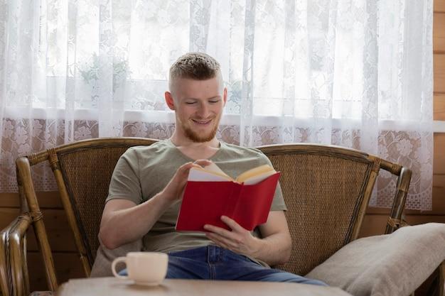Jovem sorridente lendo livro com capa vermelha em um banco de vime em uma casa de madeira do campo