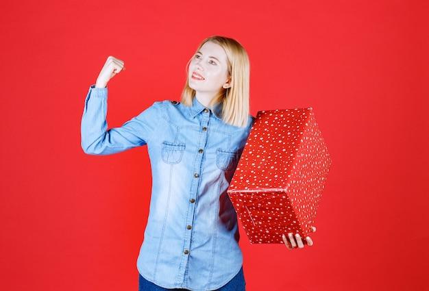 Jovem sorridente levanta o braço para mostrar os músculos e guarda a caixa de presente