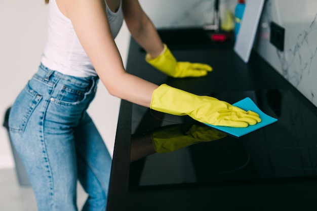 Jovem sorridente limpa a cozinha de sua casa