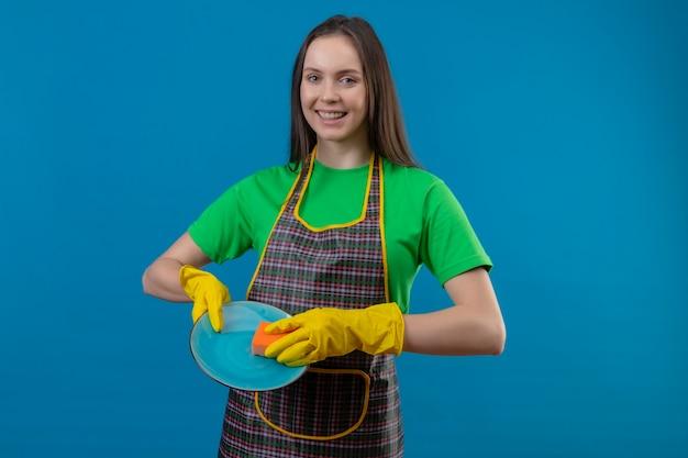 Jovem sorridente, limpando, usando uniforme com luvas, lavando pratos em fundo azul isolado