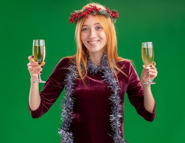 Jovem sorridente linda com um vestido vermelho com coroa e festão no pescoço segurando uma taça de champanhe isolada sobre fundo verde