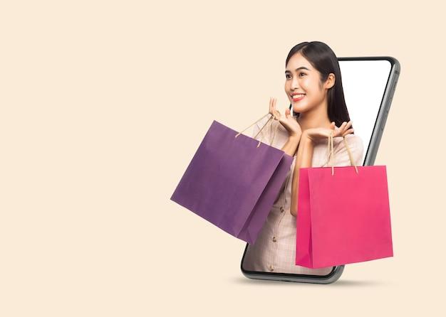Jovem sorridente linda mulher asiática fazendo compras online e segurando sacolas de compras através do telefone móvel, isolado em um fundo bege com traçado de recorte.