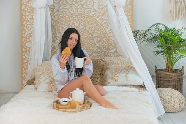 Jovem sorridente linda mulher em camisa branca, acordando de manhã, sentada na cama. linda mulher segurando croissants e bebendo uma xícara de café no quarto. conceito de estilo de vida alimentar