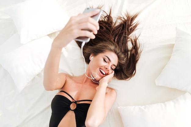 Jovem sorridente linda mulher ouvindo música com fones de ouvido e smartphone na cama da praia