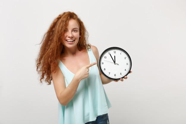 Jovem sorridente linda ruiva garota em roupas leves casuais posando isolado no fundo da parede branca, retrato de estúdio. conceito de estilo de vida de pessoas. simule o espaço da cópia. apontando o dedo indicador no relógio.