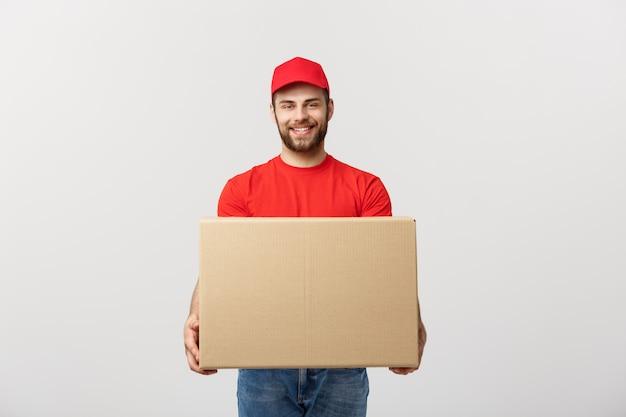 Jovem sorridente logística homem de uniforme vermelho, segurando a caixa em branco
