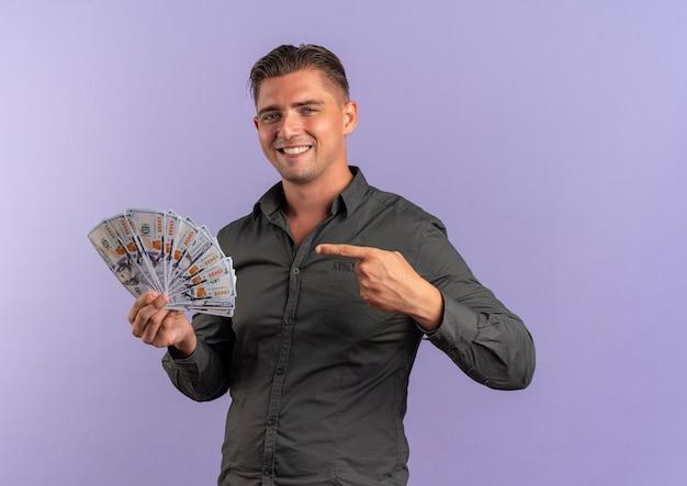 Jovem sorridente loira bonita segura e aponta para dinheiro isolado no espaço violeta com espaço de cópia