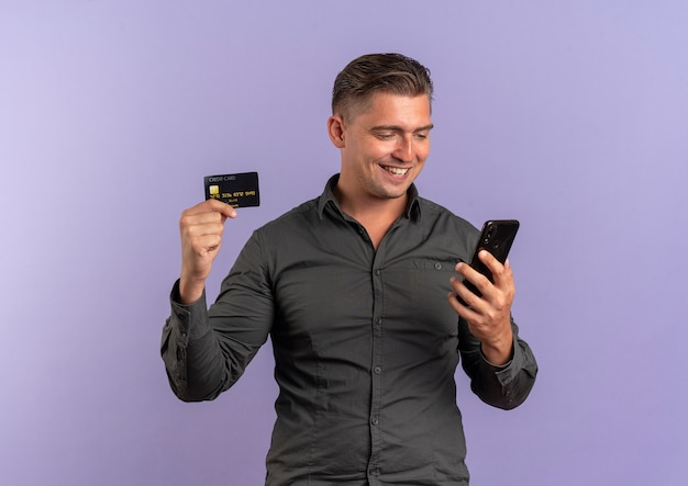 Jovem sorridente loira bonita segurando um cartão de crédito e olhando para o telefone