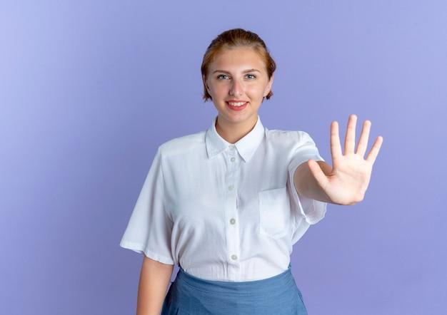 Jovem sorridente loira russa gesticulando cinco isolados em um fundo roxo com espaço de cópia
