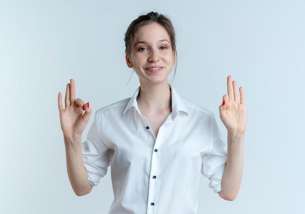 Jovem sorridente loira russa gesticulando com a mão ok sinal com as duas mãos isoladas no espaço em branco com espaço de cópia