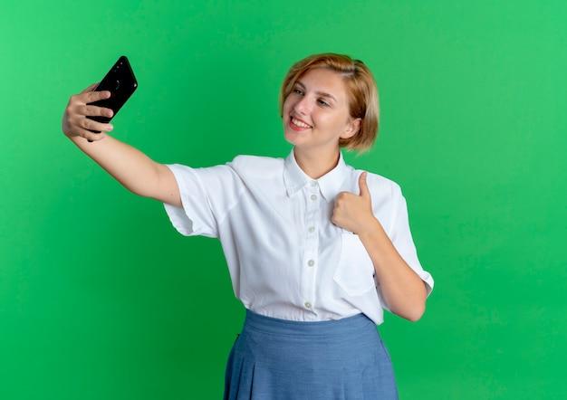 Jovem sorridente loira russa polegares para cima olhando para o telefone