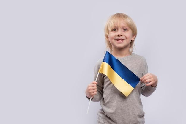 Jovem sorridente loiro segurando a bandeira da ucrânia em branco. estudo de ucraniano.