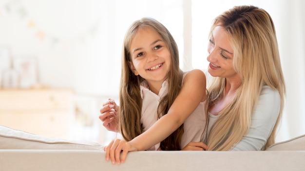 Jovem sorridente mãe e filha posando juntas