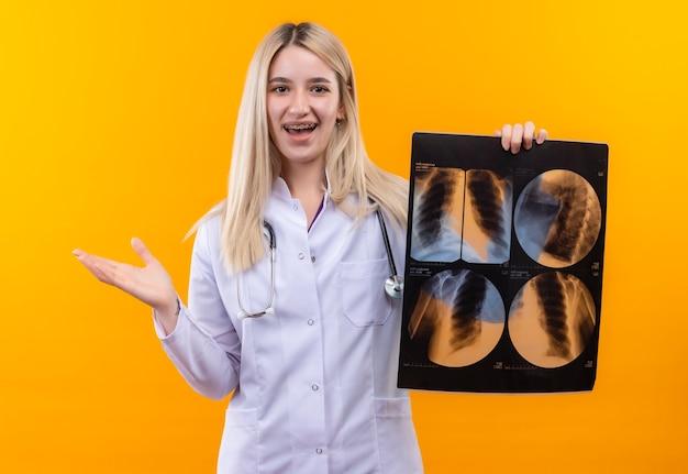 Jovem sorridente, médico, usando um estetoscópio com bata médica e aparelho dentário, segurando os pontos de raio-x ao lado no fundo amarelo isolado