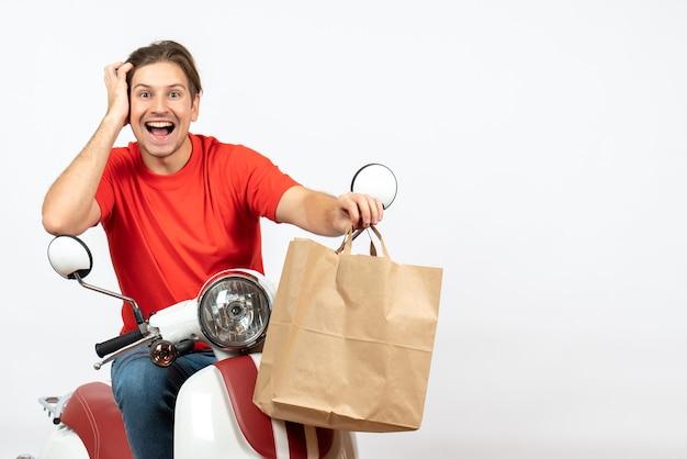 Jovem sorridente mensageiro emocional com uniforme vermelho sentado na scooter dando um saco de papel olhando algo na parede branca