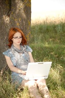 Jovem sorridente moda menina de óculos e notebook sentado perto de árvore.