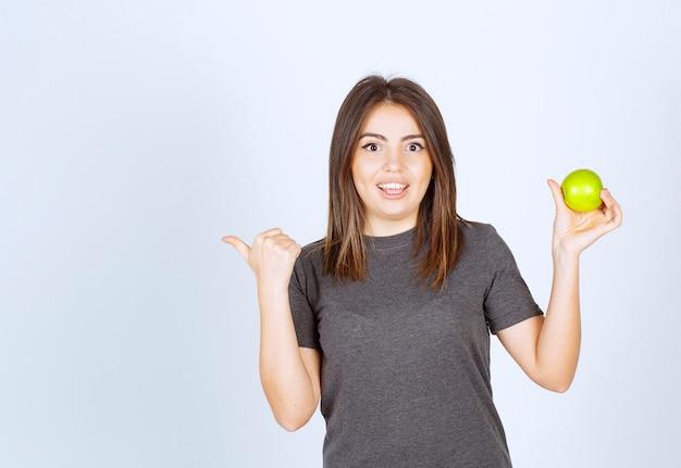 Jovem sorridente modelo mulher segurando uma maçã verde e mostrando um polegar à parte.