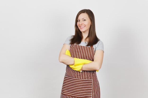Jovem sorridente morena caucasiana dona de casa em avental listrado, luvas amarelas isoladas. mulher linda dona de casa de mãos cruzadas
